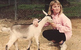 Girl feeding goat in children's zoo
