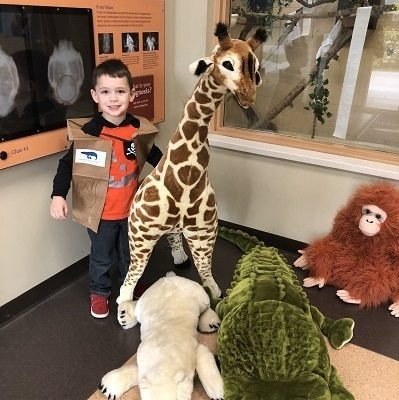 Preschool Pride kid wearing kid-crafted keeper vest with large stuffed animals